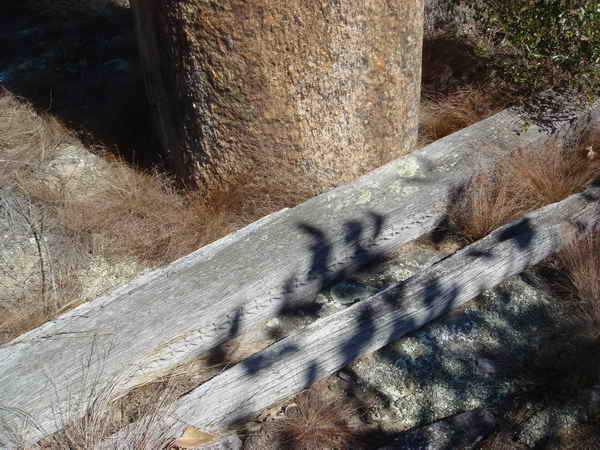 sa base est entourée d'une bordure de pierres enfoncées dans le sol, «mais il est muni d'une garniture de bois, portée par deux poteaux
